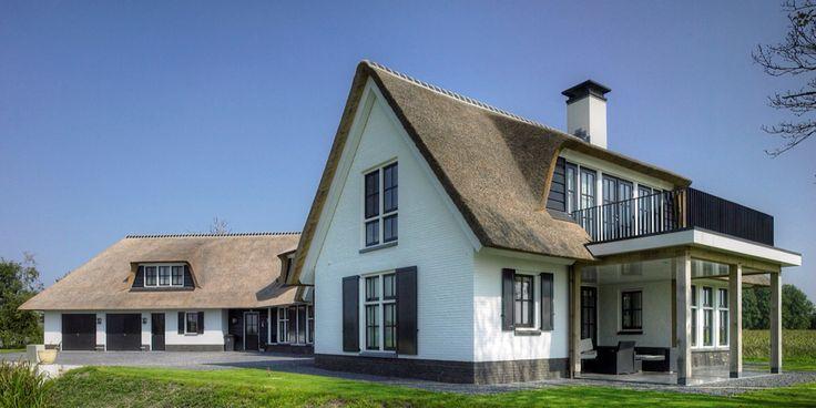 Grote witte villa met rieten dak