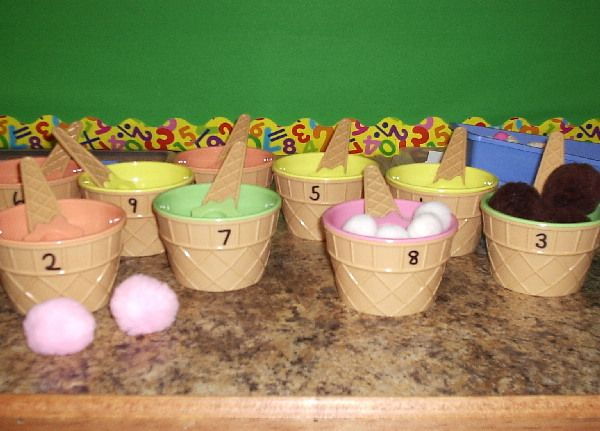 "Count ice cream scoops (pom-poms), into the ice cream cups - the spoons also have the correct number of dots written on them ("",)"