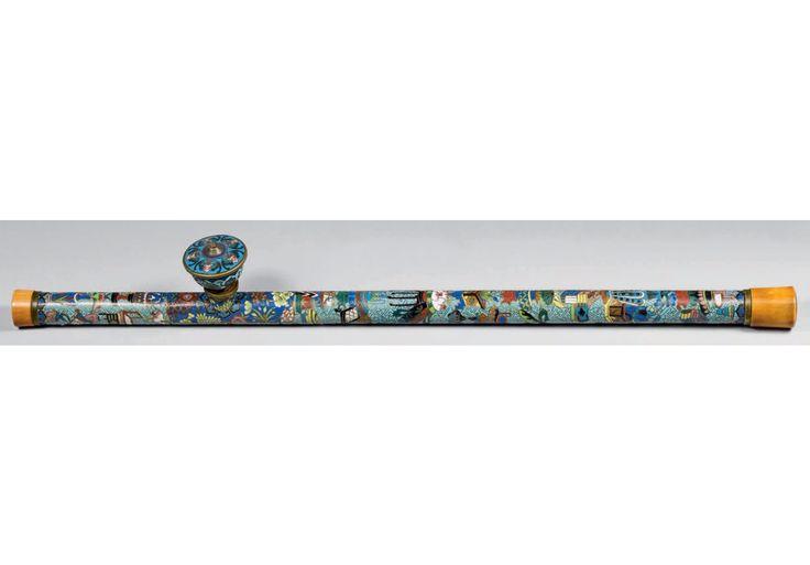 CHINE - Fin du XXe siècle  Pipe à opium en bronze et émaux cloisonnés polychromes sur fond bleu turquoise à décor d'objets mobiliers et de fleurs sur fond de svastika, la bague en cuivre, les embouts en ivoire teinté. Fourneau en bronze et émaux cloisonnés polychromes à décor des cinq chauves-souris, la bordure et l'orifice en cuivre. Longueur: 60,9 cm Vente à Drouot du 26/10/2017 Beaussant Lefèvre OVV Estimation : 800 / 1 200  €