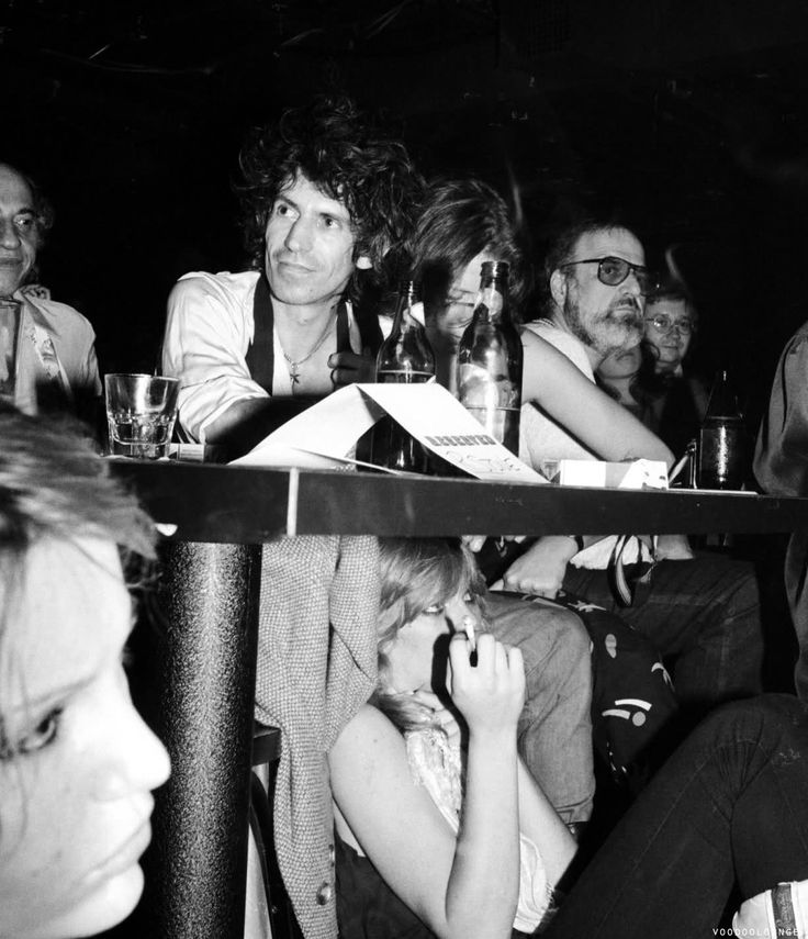 Keith Richards with Jane Rose next to him and Patti Hansen sitting against his legs attend The Rolling Stones' 'Emotional Rescue' album release party for members of the press at Danceteria on June 26, 1980 in New York City.