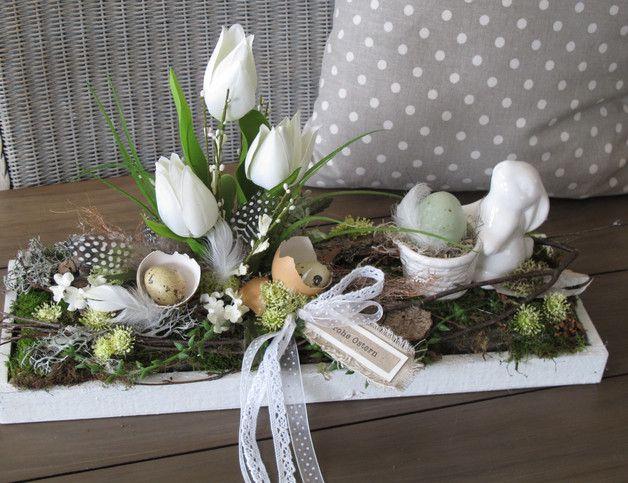 """weißes Holztablett im shabby-Style  dekorativ """"bepflanzt""""  mit einem süßen Keramikhasen der ein Ei vor sich trägt,  weißen Tulpen, Gräsern, weißen Blüten, verschiedenen Eiern,, Federn und..."""