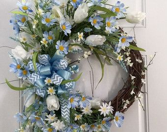 Feeling Blue? This beautiful and airy Daisy and Tulip wreath will cheer you in no time! Sky blue daisies and white tulips, cherry blossoms, and lots of leafy greenery are just bursting from this beautiful wreath. In the center, a large bow of powder blue chevron ribbon and blue satin ribbon brings it all together. This beauty will grace your entrance and be the herald of spring at your home. Measuring from highest stem tip to the very lowest, it measures 30 inches and about 22 inches across…