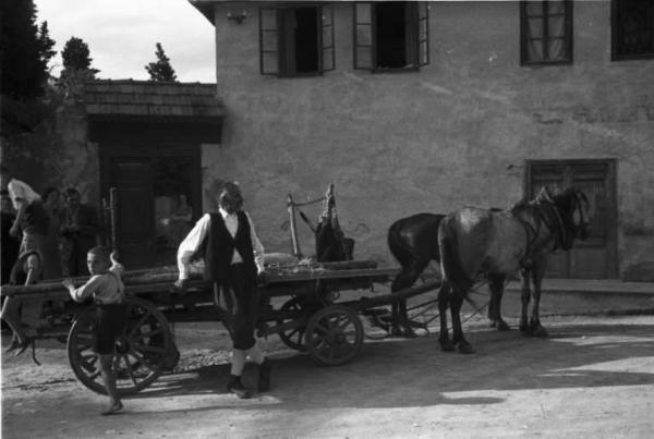 Viaggio in Jugoslavia. Mostar: scene di vita quotidiana - un uomo e un bambino si riposano accanto a un carro trainato da una coppia di cavalli.