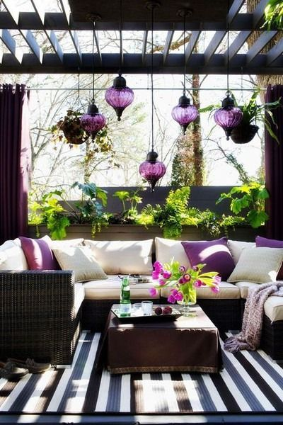 Outdoors, sun room, three season room, lanterns, plants, striped rug, wicker outdoor couch, hippy, bohemian, purples, creams