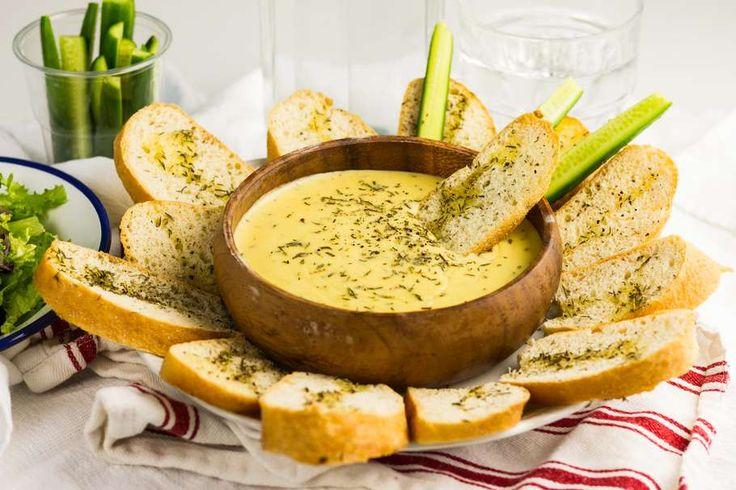 Recept voor kaasfondue voor 4 personen. Met suiker, water, peper, kaas, eikenbladsla, wit brood, witte wijn, tijm, ui, knoflook, Dijon mosterd en komkommer
