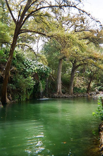 Krause Springs in Spicewood, Texas - Situated on a bluff overlooking Cypress Creek, with the water spilling down a bluff over ferns and then crashing into a deep pool. Tent and RV camping is available in the park.