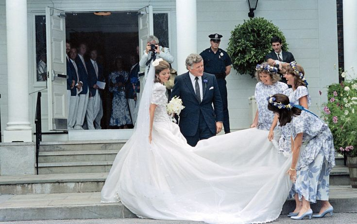 Caroline Kennedy, in a dress scattered with shamrocks and designed for her by Carolina Herrera, with her uncle Senator Ted Kennedy, who gave her away to Edwin Schlossberg, outside Our Lady of Victory Church in Centerville, Massachusetts, in 1986.