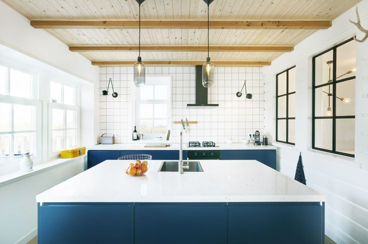 Modern kitchen design, white marble table top. White tiles, wooden beams and design lamps.  Design by BNLA architecten, photography Wim Hanenberg.