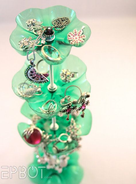 Create a jewelry stand from the bottoms of Mountain Dew bottles; just thread them together with a metal rod.
