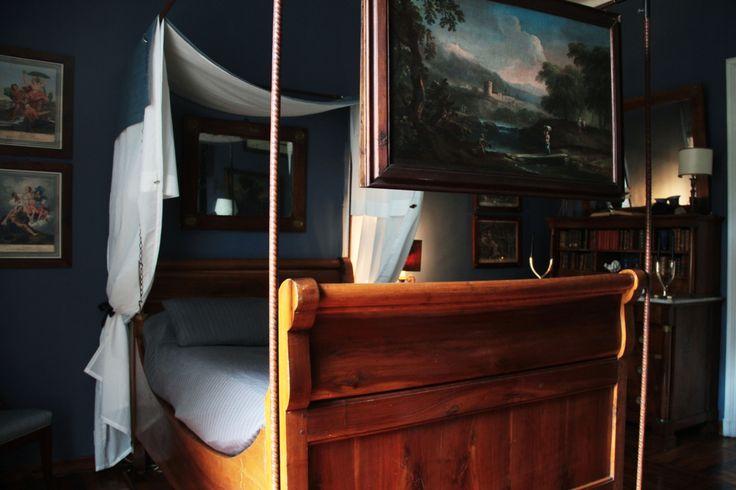 Dettaglio: quadro antico appeso alla struttura in tondini di ferro che contorna un letto a barca di fine '700