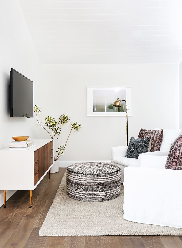 Small TV room with white sofa, ottoman, indoor plant, and modern floor lamp p