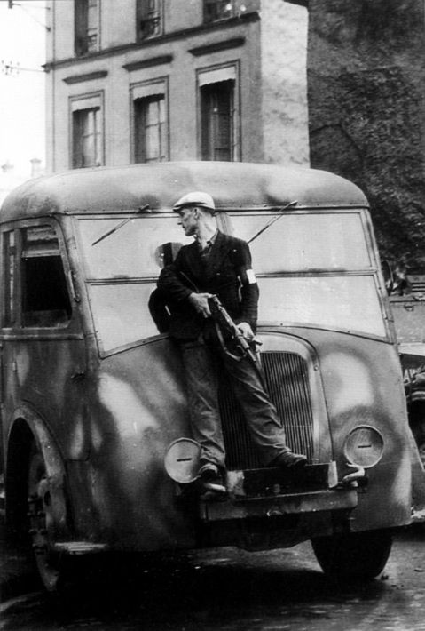 A French resistance maquis armed with a STEN gun shelters behind a truck while taking on German snipers in the town of Dreux