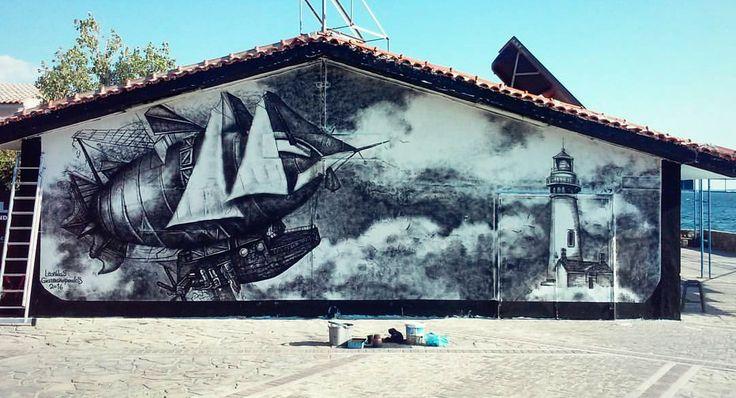 """Απόφοιτος της Ανωτάτης Σχολής Καλών Τεχνών και ειδικός στην τέχνη της σύγχρονης τοιχογραφίας graffiti, ο Leonidas Giannakopoulos μεταμόρφωσε κυριολεκτικά πριν από λίγες ημέρες τις εγκαταστάσεις των πρώην αμερικανικών βάσεων στο θαλάσσιο μέτωπο της Ελευσίνας σε καμβά της τέχνης του δρόμου. Το έργο του με τίτλο """"Promised Land Is A State Of Mind"""" επιχειρεί να ανοίξει έναν εικαστικό διάλογο για τη μαζική μετακίνηση μεταναστών πολέμου και την αναζήτηση της Γης της Επαγγελίας."""