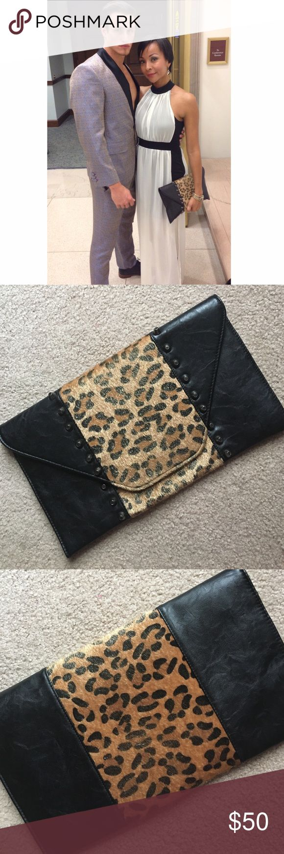 """Animal Print Leather Studded Clutch This amazing piece will spice up any outfit! Leather and faux fur construction with studs embellishment in front,  flap and zip closure, and pockets for coins and cellphone inside. Fully lined, 14"""" x 8"""" Bags Clutches & Wristlets"""