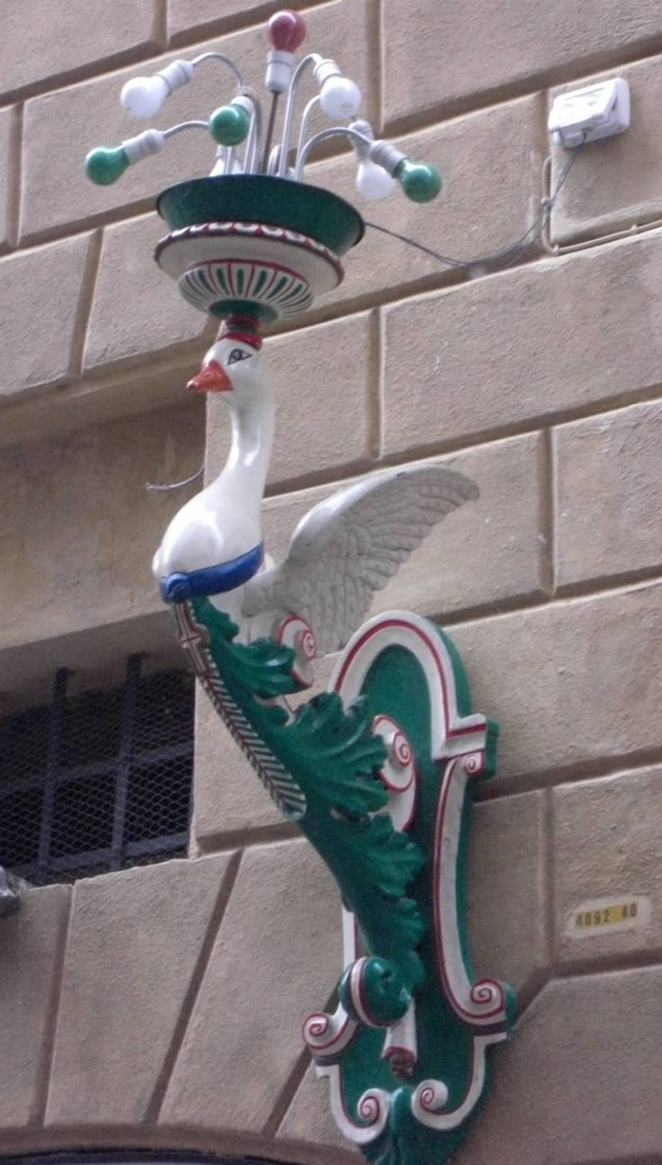 "Siena, Italy is comprised of 17 ""contrade,"" a district or ward within a city. This is a street light fixture in Oca (the goose), situated just to the west of the Piazza del Campo. Traditionally, its residents made dyes. Oca's symbol is a crowned goose wearing around its neck a blue ribbon marked with the cross of Savoy. Its colours are green and white, with red trim."