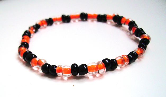 Elastic bracelet with glass beads in orange and black.  Customizable size. The bracelet on display is for a wrist measuring small-medium.  Customizable colors. Do I have the colors: blue, red,...