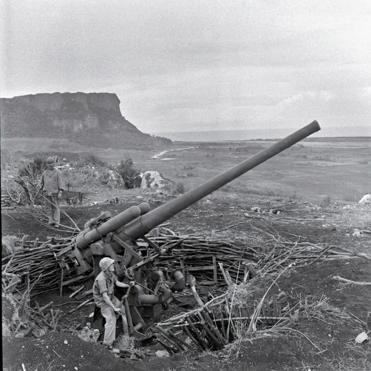 A crew maneuvers an enormous piece of artillery during the Battle of Saipan, 1944. In the waning days of the struggle for the island, thousands of Japanese civilians and troops committed suicide, rather than surrender to American troops. Many leapt to their death from the top of sheer cliffs that fall 200 feet to rocks and surf below.
