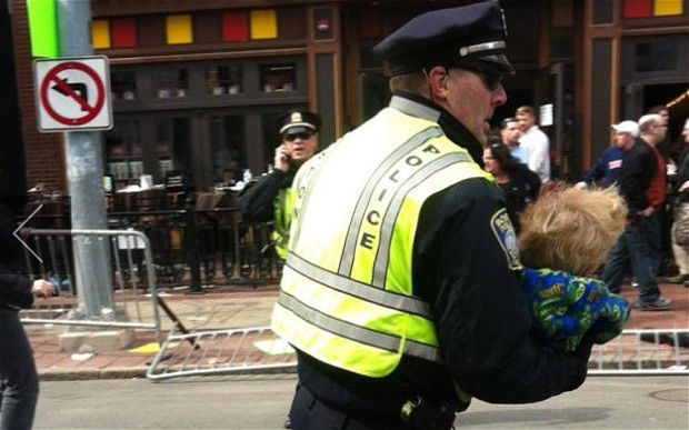 A police officer carries a child to safety after the Boston Marathon bombings