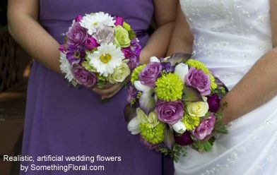 Round bridal bouquet designed with lavender roses, purple ranunculus, green chrysanthemums, white tulips, purple lilacs, purple and white bi-color calla lilies, and maiden hair fern. Coordinating bridesmaid bouquets contained a similar mix of floral varieties plus white gerbera daisies and purple cosmos. #bridal #bouquet #bridesmaid #purple #green #lavender #white #wedding #flowers