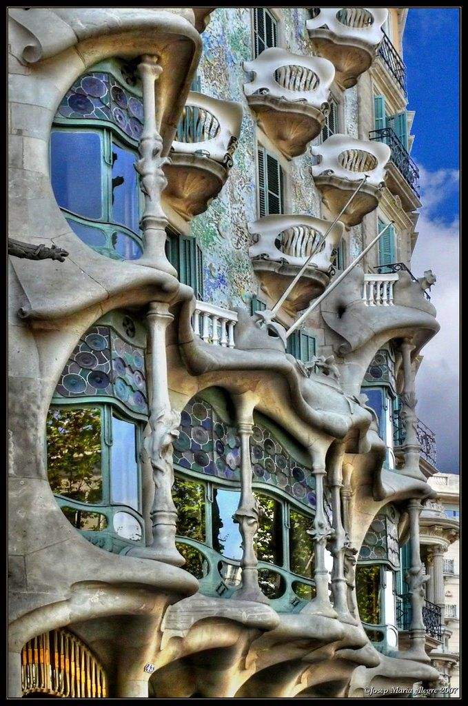 """'Casa Batlló' Antoni Gaudí 1906. Joinery windows set with multicolored stained glass. In front of the large windows, as if they were pillars that support the complex stone structure, there are six fine columns that seem to simulate the bones of a limb, in fact, this is a floral decoration. The rounded shapes of the gaps and the lip-like edges carved into the stone surrounding them create a semblance of a fully open mouth, for which the Casa Batlló has been nicknamed the """"house of yawns."""""""