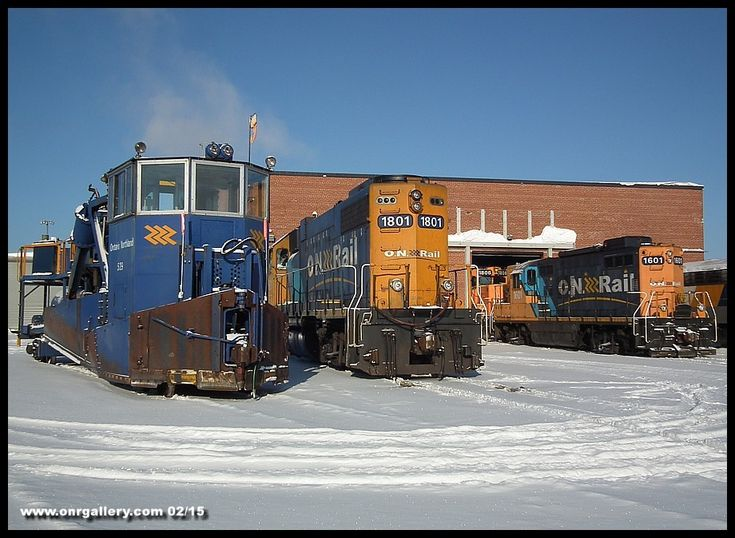 We're at the south side of Cochrane Shops on February 22, 2014 where we're greeted by a wide variety of equipment. On the left, spreader 529 sits quietly now complete with new flags on her front end while GP38-2 1801 sits on Shop #1. GP9 1601 is being used to bring GP38-2 1806 into Shop #3, and APU 205 sits on Shop #4 with 2 coaches ready for a 999 to Moosonee later in the day.