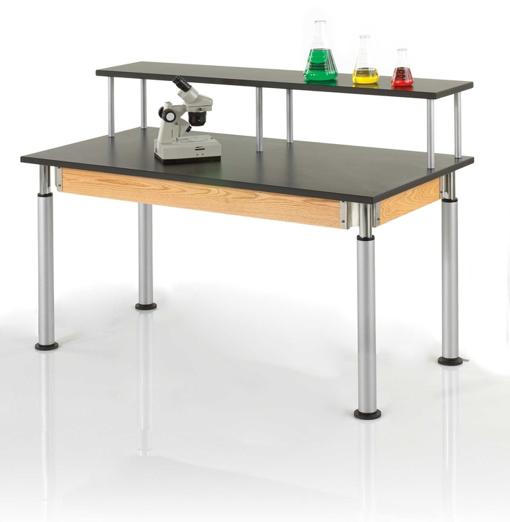 """This table has the ability to adjust in 2cm increments from 27''H to 39''H in less than 30 seconds. Add 3"""" spacer for even more height. The 4-1/2''H solid oak frame with exposed metal corner braces compliment the powder-coated adjustable legs with adjustable glides. The wood is finished with a chemical resistant, earth-friendly UV finish. It has a riser that provides extra workspace for each person to put his or her tools or laptop.   (DW_PR8144k)"""