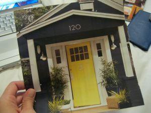 yellow door, mat, plants, white trim, modern numbers