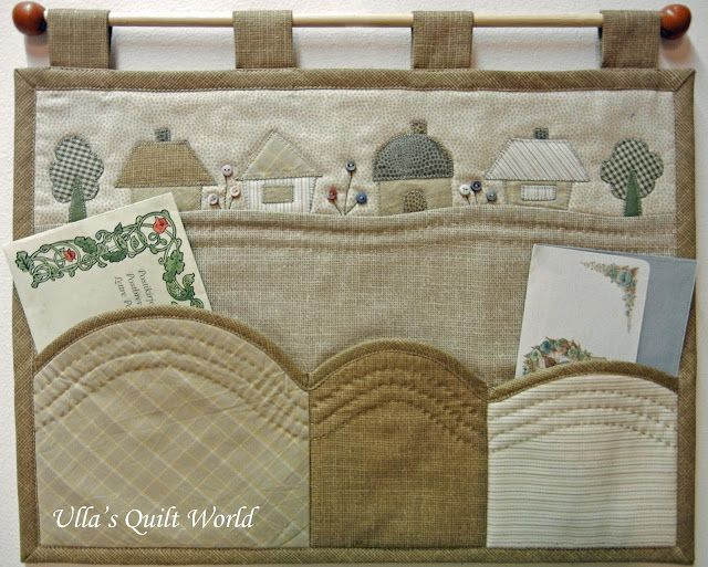 Wall hanging quilt with pockets - love the strip of little houses!!