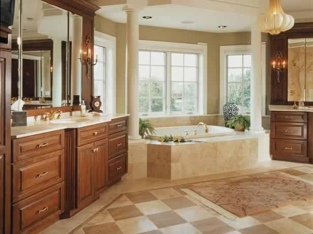 Dos columnas enmarcan la bañera de hidromasaje, que establece el punto focal de este baño principal dramático. Gabinetes de cerezo y mármol materiales contador ayudar a hacer esta gran sala sentirse cómodo.