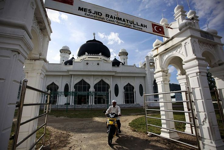 Pedestrians walk past Mosque Rahmatullah in Banda Aceh, Indonesia. Mosque Rahmatullah was the only building left standing after the tsunami in Lampuuk in December 2004.