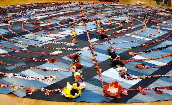 Janice and Lois, two Veriditas Accredited labyrinth Facilitators built a portable eleven circuit Chartres style labyrinth! It is created from recycled blue jeans, patched or quilted together to make the base. The 11-circuit Chartres pattern is made from a braided cord made from donated fabric, clothing and trim. The flowers were made from donated bras of all colours and sizes. http://www.facebook.com/pages/Labyrinth-Project/226201742364?sk=info#!/pages/Labyrinth-Project/226201742364