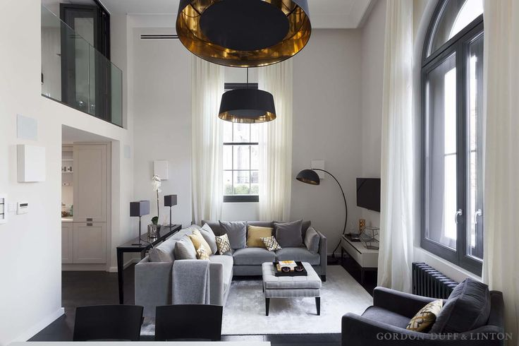 New mezzanine level for bedroom over-looking living room in Victorian conversion in central London. Black pendant lamps with gold interiors. Grey L-shaped sofa with yellow cushions. Double-height arched windows.