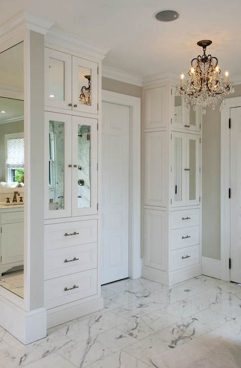 Dream bathroom with floor to ceiling built-ins featuring lower drawers under mirrored cabinets on either side of the doorway over white and gray marble tiled floors illuminated by a wrought iron and crystal chandelier.