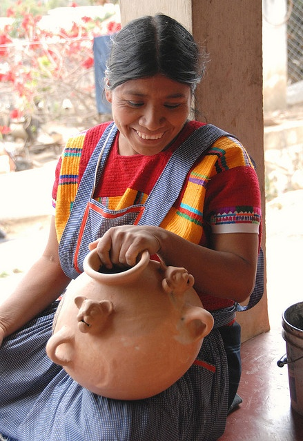 a Maya woman laughs as she paints a jaguar olla. Amatenango del Valle Chiapas Mexico