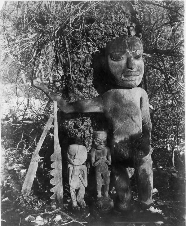 "Large figure is Gou-ghe yah-tee, ""drum holder"". The drum of the shaman was hung on the outstretched arms These figures were known as ut nuh teen, ""he sees some-thing,"" and were made for very special occasions (G. T. Emmons, The Tlingit Indians)."