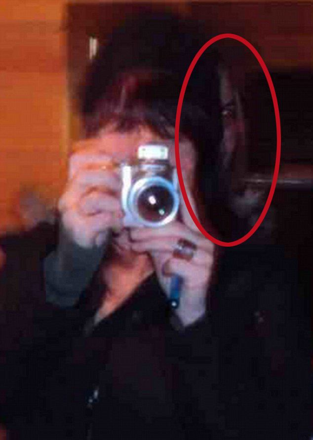 The photo of an unknown woman shows her taking a photo in the mirror with her camera. Behind her left shoulder, what looks like another woman's face can be made out with glowing eyes and a sinister grin.
