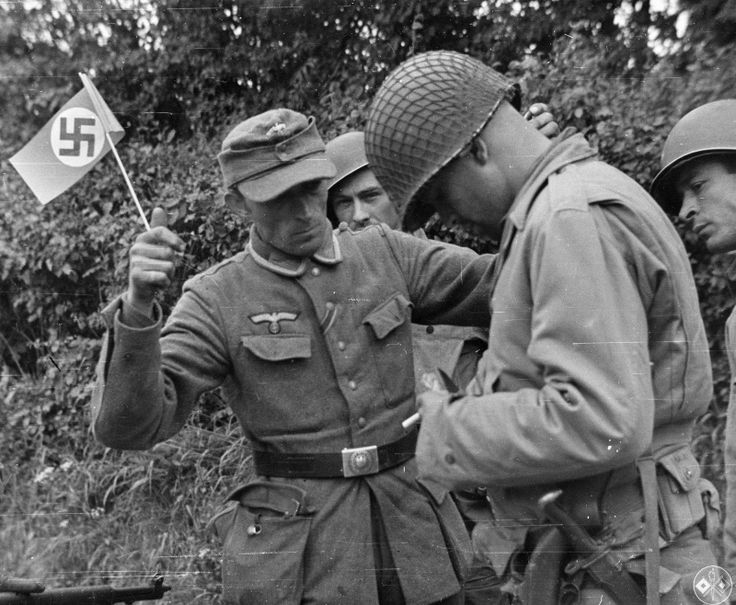 Non-commissioned officer of the Wehrmacht with the Nazi flag surrender to American soldiers in France.