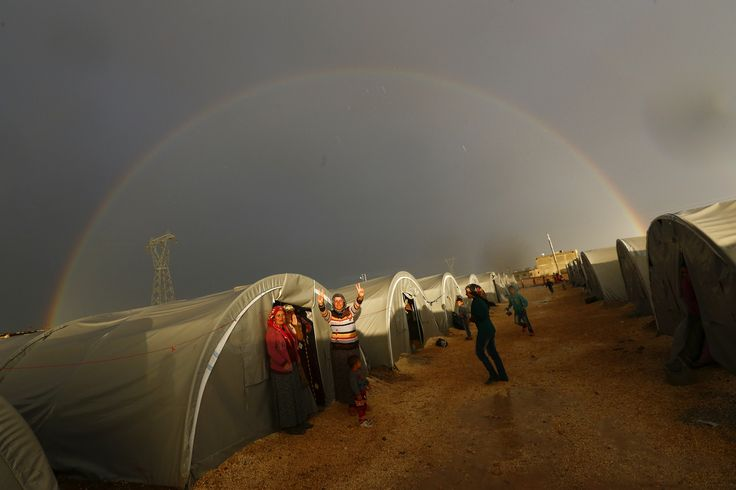 A Kurdish refugee from the Syrian town of Kobani shows the victory sign as a rainbow forms over the refugee camp in Suruc, Sanliurfa province, Turkey.
