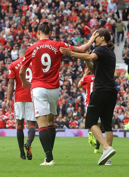 Zlatan Ibrahimovic of Manchester United shrugs off a pitch invader during the Premier League match between Manchester United and Leicester City at...