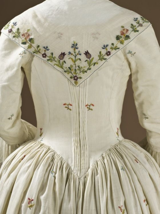 Detail back view, robe à l'Anglaise ensemble, England, 1780-1790. Polychrome wool crewel embroidery with floral sprays on white linen.