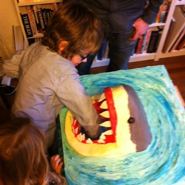 My son Ben is crazy about wildlife and his favourite TV show is Deadly 60 with Steve Backshall, so a Great White Shark was the perfect specimen for his 7th birthday cake. I built it as if it was breaching out of the water to attack and wanted to add a playful twist to the occasion so I added a lucky dip game inside the stomach of this tasty apex predator - the idea being that the kids would have to carefully put their arm into the belly of the beast and fish out squidgy treats without to...