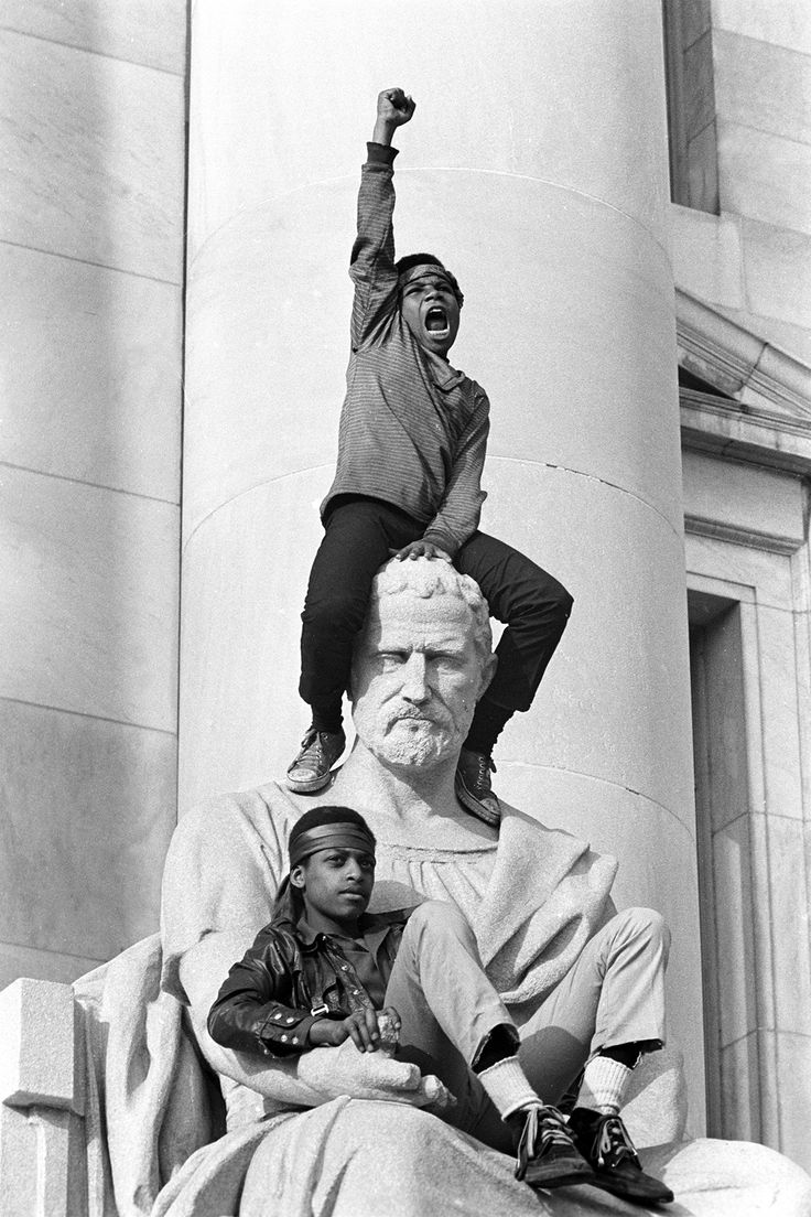 A boy giving a raised fist salute as he and a friend sat on a statue in front of the New Haven County Courthouse at a demonstration of 15,000 people during the trial of Bobby Seale and Ericka Huggins. Both were acquitted. May 1, 1970. —Stephen Shames