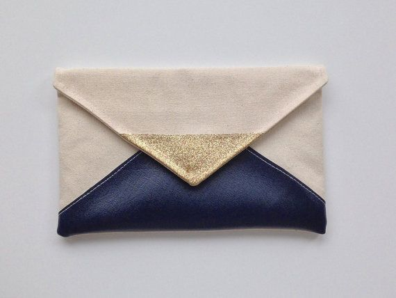 This Envelope style clutch is made out of natural canvas, with glitter and navy blue vinyI accents. It features a cotton lining, magnetic snap and