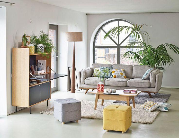Un canapé en tissu gris chiné aux lignes rebondies dans un salon esprit scandinave avec plantes vertes
