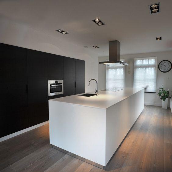 Prachtig wit kookeiland en zwarte kasten. Door de houten vloer brengt het deze 2 harde kleuren mooi bij elkaar! - www.fairwood.nl