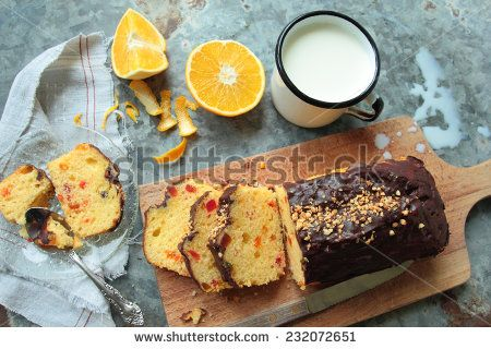 Homemade fruit cake with chocolate glaze and mug of fresh milk - stock photo