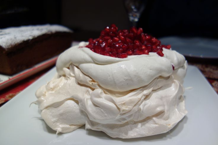 Crisp and delicate Pavlova with a dollop of vanilla whipped cream and fresh pomegranate