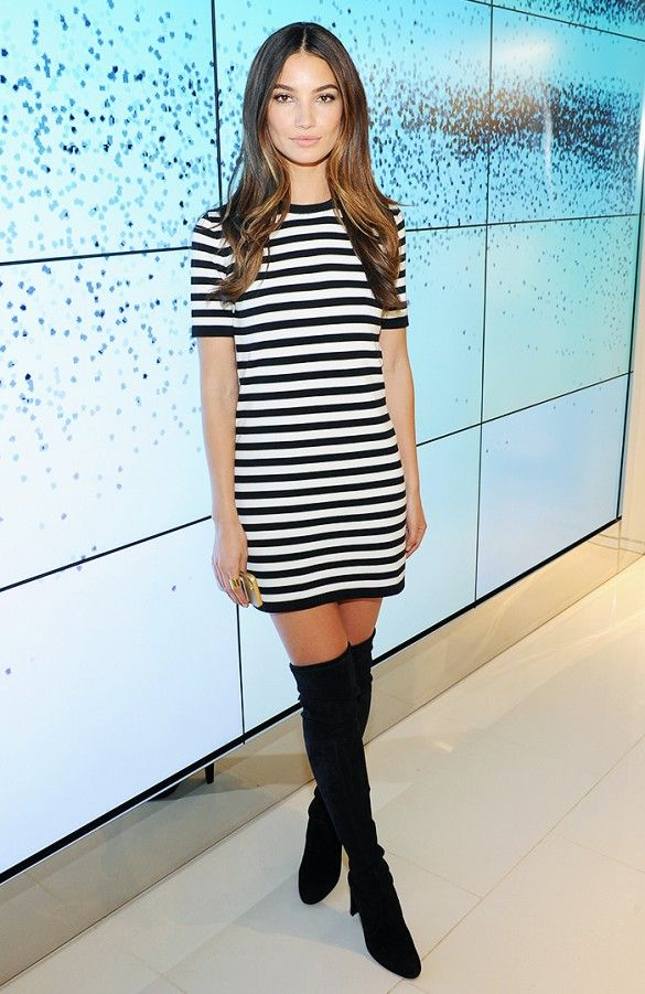 Lily Aldridge wears a striped mini dress and over-the-knee boots