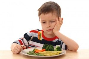 está enojado, no quiere comerse las verduras, lo obliga, no le permite que se levante de la silla - Inference: How do you think this boy feels about his dinner? What makes you think so?