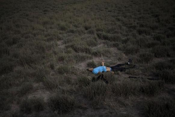 WARNING: GRAPHIC CONTENT The body of a dead man, with a rifle next to him, lies in a field after a shootout with police on the outskirts of Monterrey February 28, 2012. According to local media, 11 people were killed in different violent incidents in the city.   REUTERS/Daniel Becerril